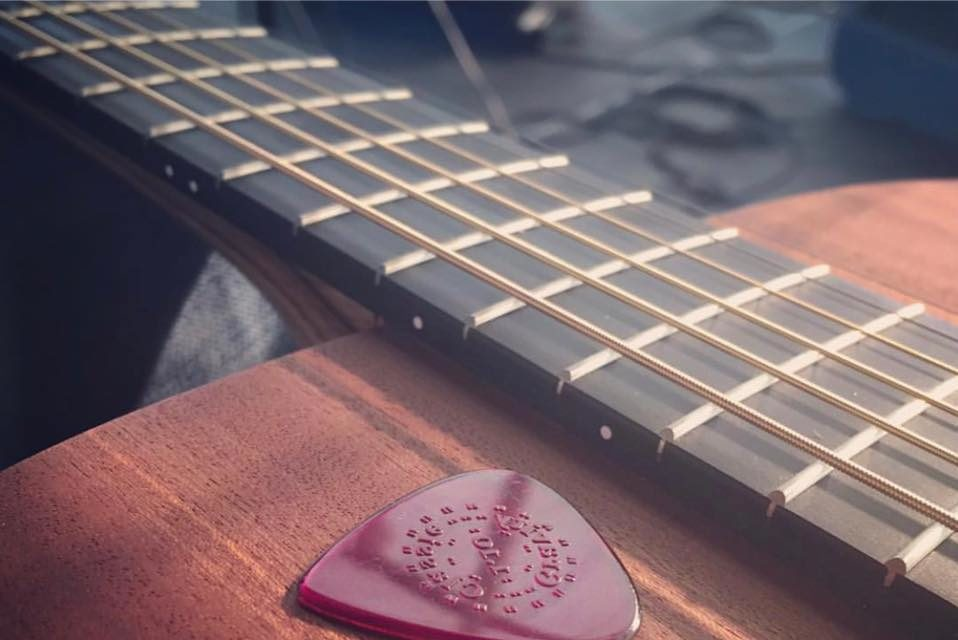 acoustic guitar and plectrum to be played at a wedding